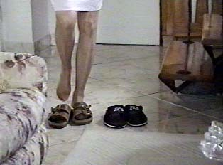 Woman removing slippers in front of carpet inside a home(not as common but also done)