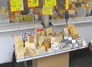 An outdoor market stand displaying variety of cheese