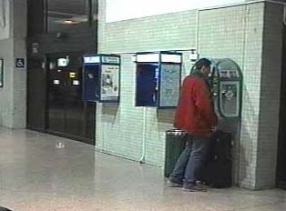 Man using public payphone in airport
