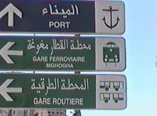 Directional signs on the roadway both in Arabic and Roman script