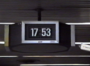 A small black digital clock, displaying time in the 24-hour system