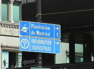 A blue sign directing people to tourist information center and a planetarium