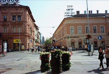 A pedestrian street in Hungary, with several people and buildings