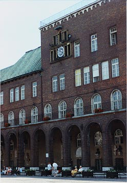 The front of a brick building with an analog clock, with a few people sitting alongside the street