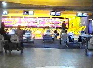Several people sitting in front of bowling lanes, inside a bright bowling alley