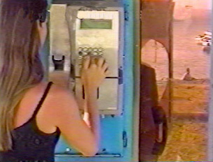 A person dialing on a pay phone