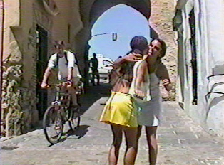 Two people hugging on a small street