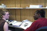 A student and a language mentor sitting at a desk having a discussion